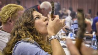 Женщина курит кубинскую сигару