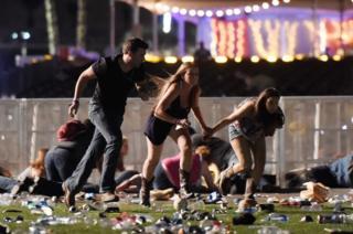Three people run for cover as gunfire reins down.