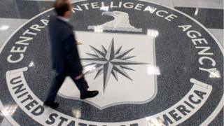 A man crosses the Central Intelligence Agency (CIA) seal in the lobby of CIA Headquarters