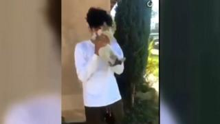 Boy in white shirt holds cat before throwing it.