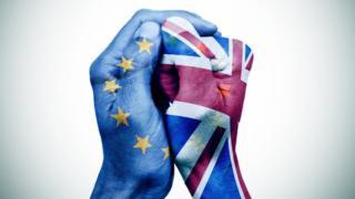 Mãos com as bandeiras da UE e do Reino Unido
