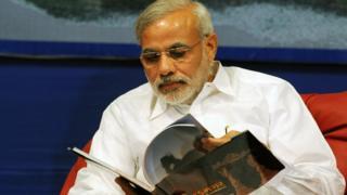 Narendra Modi leafing through a book