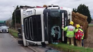 Emergency services attend an overturned lorry with part of its windscreen smashed