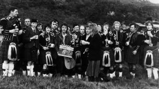 Denny Laine, Paul McCartney and Linda McCartney with the Campbeltown pipe band during the filming of the video