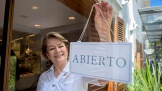"""Una mujer sostiene un cartel en un comercio que dice """"abierto""""."""