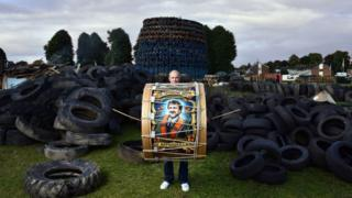 Barry from Kells beats a Lambeg drum in front of the Ballycraigy housing estate bonfire in Antrim, County Antrim.