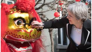 "Prime Minister Theresa May ""dots the eye"" of a Chinese dragon"