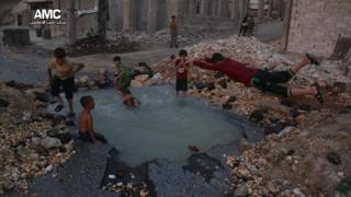 Photograph published by Aleppo Media Centre showing Syrian boys diving in a water-filled crater in the Sheikh Saeed district of Aleppo on 31 August 2016