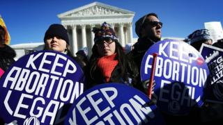 Pro-choice activists hold signs as marchers of the annual March for Life arrive in front of the US Supreme Court.