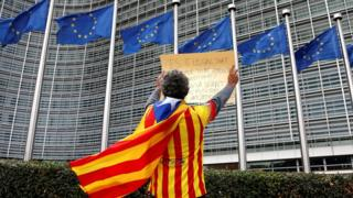 A man draped in a Catalan independence flag protests outside the European Commission in Brussels, 2 October