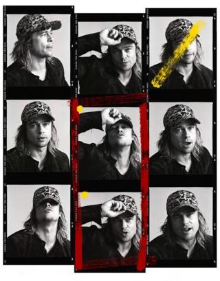 Brad Pitt poses in a cap