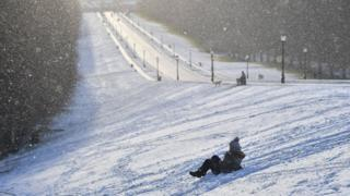 Someone sledging down a slope
