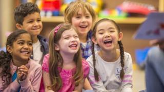 Children listening to a teacher reading a story