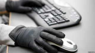 Hands with black gloves on computer keyboard and mouse