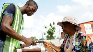 Woman wey dey vote with electronic voting machine wey INEC official dey help for Nigeria