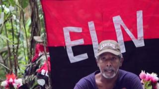 TV grab of Odin Sanchez in front of an ELN flag