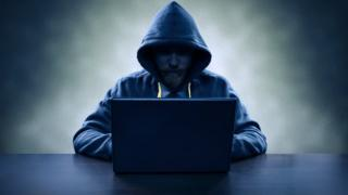 hooded man with lap-top