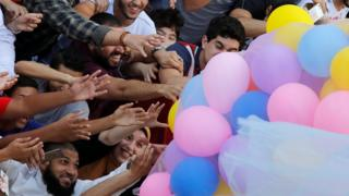 Egyptians celebrate and try to catch balloons released after Eid al-Fitr prayers, marking the end of the Muslim holy fasting month of Ramadan at a public park, outside El-Seddik Mosque in Cairo, Egypt June 25
