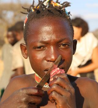 Criança hadza comendo carne vermelha