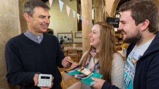 A Church of England vicar accepts a cashless payment