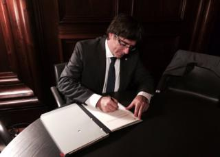 Catalan President Carles Puigdemont signs the bill into law, 6 September