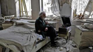 Mohammad Mohiedine Anis, 70, mengisap pipa sambil duduk di kamar tidurnya yang hancur dan mendengarkan musik di pemutar rekamannya di Aleppo.