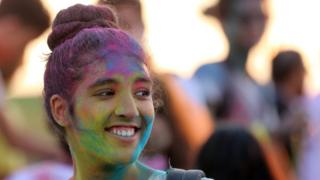 A Festival-goer is covered with colored powder during the music and color festival at the Golf Citrus in Hammamet south of Tunis, 27 Tunisia August 2016