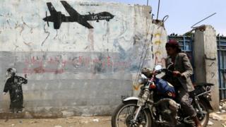Yemeni rides motorcycle past graffiti protesting against US drone operations in Yemen. 5 September 2016