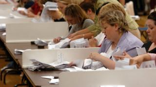 People count the votes on ballot papers during election