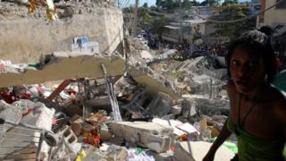 Haitians pass destroyed buildings on January 13, 2010 in Port-au-Prince, Haiti.
