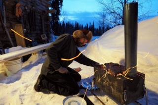 David lights a fire outside