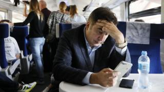 Former Georgian president Mikheil Saakashvili presses a hand to his forehead while looking at his mobile phone aboard a train to in Przemysl, Poland