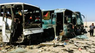 Burnt-out buses at the scene of a suicide blast in Samarra on 6 November 2016