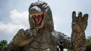 Crewmember Tetsuo Hayashi airbrushes the final touches to a 6.6 meter replica of the famous Godzilla at Tokyo Midtown on July 15, 2014 in Tokyo, Japan.