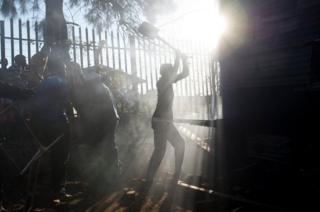A resident tries to extinguish a fire in Atteridgeville