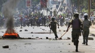 Riot police chase protesters calling for the disbandment of the national electoral commission over allegations of bias and corruption, in Kisumu, Kenya Monday, June 6, 2016