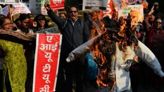 Indian activists shout slogans during a protest as they burn an effigy of the chief minister of Haryana Manohar Lal Khattar in New Delhi on January 17, 2018, against the gang-rape of two schoolgirls in the neighbouring state of Haryana.