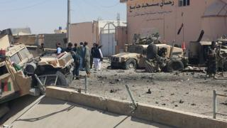 Afghan security personnel inspect the site of a suicide attack near the main police headquarters in Lashkar Gah, capital of Helmand province, 23 August 2017