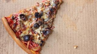 Un pedazo de pizza fría en una caja