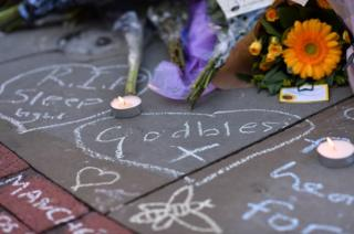Candles flicker alongside a carpet of flowers and messages at St Ann's Square in Manchester, north-west England