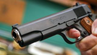 "A salesperson holds a Remington handgun at Chuck""s Firearms in Atlanta, Georgia, USA, 13 February 2018."