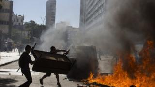 Demonstrators set a road block on fire outside the state legislature in Rio de Janeiro, Brazil, 6 December