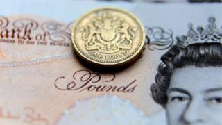 A pound coin resting on a Scottish ten pound note.