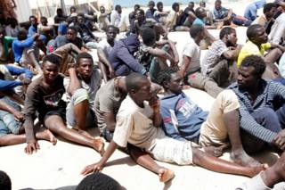 Migrants sit at a naval base after they were rescued by the Libyan coastguard in the coastal city of Tripoli, Libya