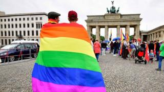 People wrapped in gay pride flag at the Brandenburg Gate, Berlin, Germany