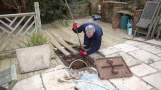 man clearing drain