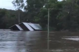 A house being swept away by floodwaters in Australia