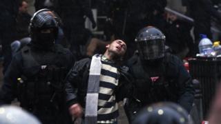 Kosovar policemen detain a man at the Vetevendosje headquarters