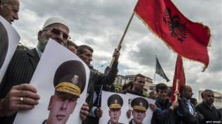 Kosovan protesters wave the Albanian flag and hold portraits of former Kosovo Liberation Army commander Sylejman Selimi during a demonstration in front of Kosovo's parliament on 29 May 2015