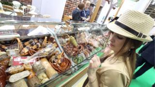 женщина смотрит на колбасные изделия